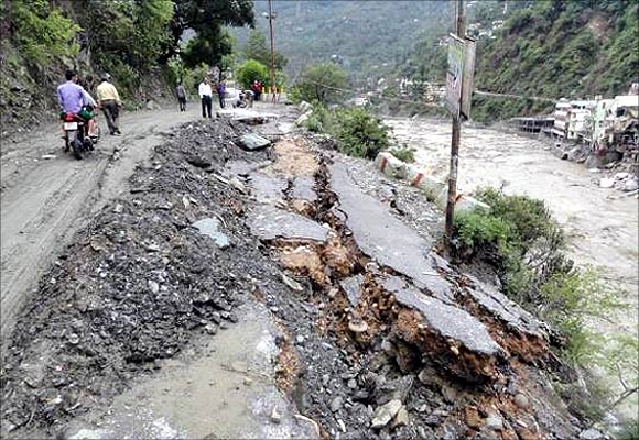 People walk along a damaged road after heavy rains in Uttarakhand.