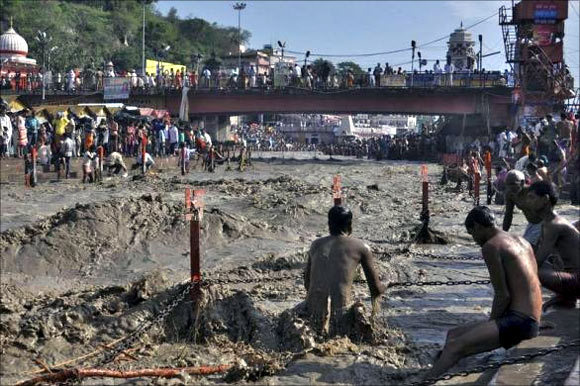 A Hindu devotee tries to take a holy dip in the flooded waters of river Ganges in Haridwar.