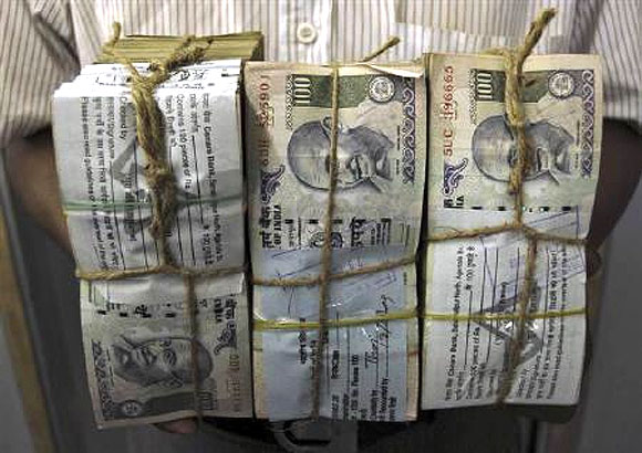An employee carries bundles of Indian currency notes inside a bank in Agartala.
