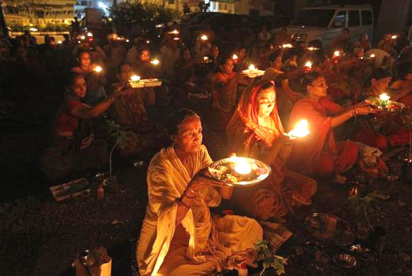 People carry oil lamps as they pray for the flood victims.