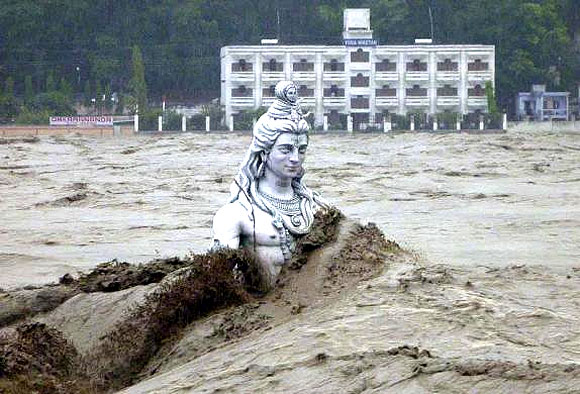 A submerged statue of Lord Shiva stands amid the flooded waters of river Ganges at Rishikesh.