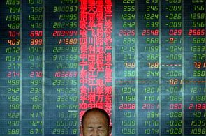 An investor reacts in front of an electronic board showing stock information at a brokerage house in Taiyuan, Shanxi province