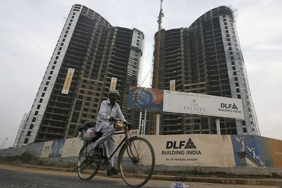 A man cycles past the construction site of a residential apartment building by Indian property developer DLF.