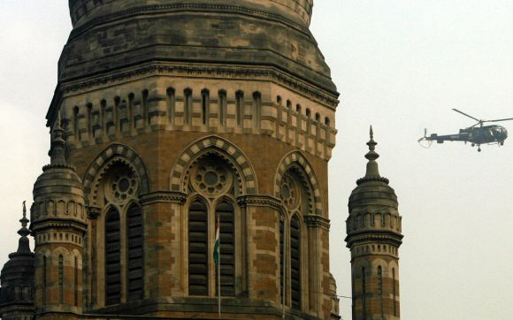 A helicopter flies past the dome of Mumbai Municipal Corporation's building.