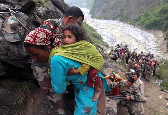 Soldiers assist a woman carrying a child on her back during rescue operations in Govindghat in the Himalayan state of Uttarakhand.