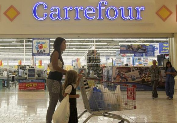 Shoppers walk in front of the Carrefour store.