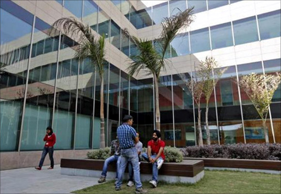Employees chat during their lunch break inside Tech Mahindra office premises in Noida on the outskirts of New Delhi.