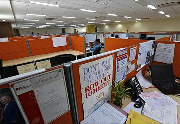 Employees work at their desks inside Tech Mahindra office building in Noida on the outskirts of New Delhi.