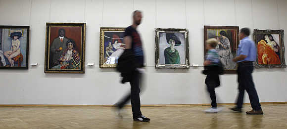 Visitors walk past impressionist paintings in the State Hermitage Museum in St Petersburg, Russia.
