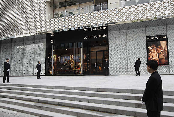 Security guards stand in front of the largest Louis Vuitton store in China in Shanghai.