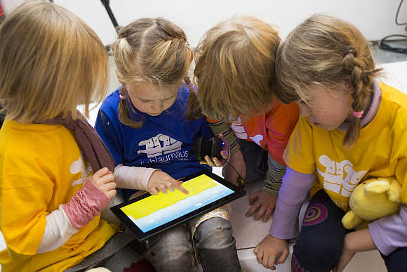 Children play with Microsoft's 'Schlaumaeuse' education software that runs on a Windows 8 operated tablet computer during the program's presentation in Berlin, Germany.