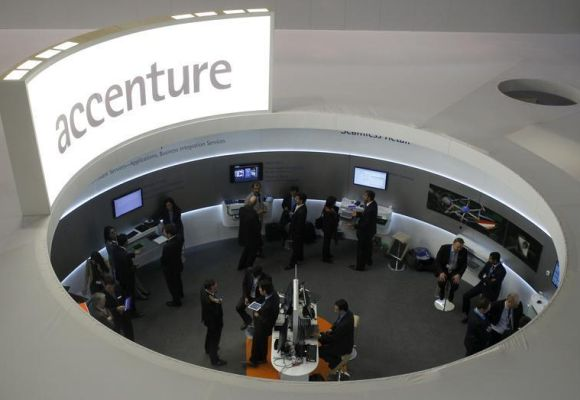 Visitors look at devices at Accenture stand at the Mobile World Congress.