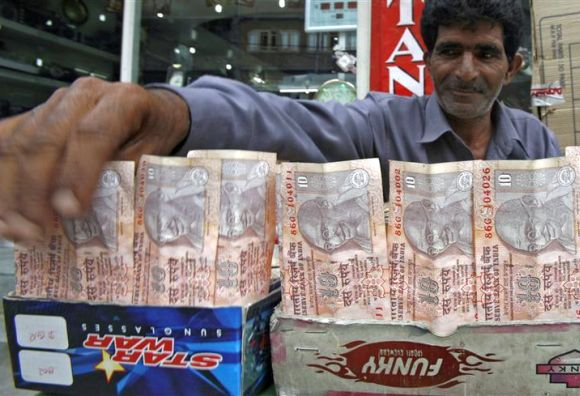 A Kashmiri money changer Nissar Ahmad displays newer Indian rupee notes in Srinagar.