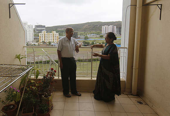Suresh Chitre, 67, and his wife Rekha Chitre, 63, stand on the balcony of their flat at the Athashri retirement village in Baner, on the outskirts of Pune.
