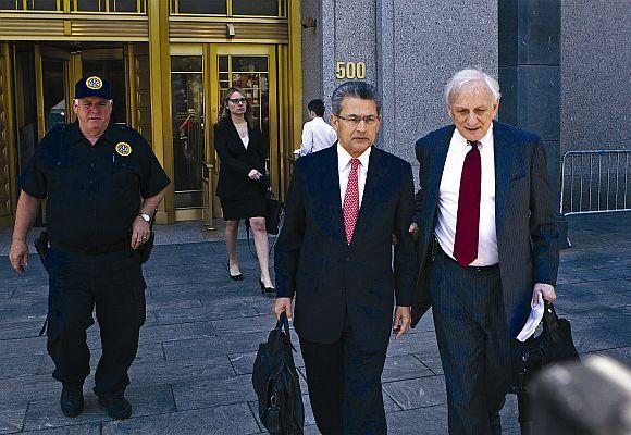 Rajat Gupta (2nd R) leaves Manhattan Federal Court with his lawyer, Gary Naftalis (R).