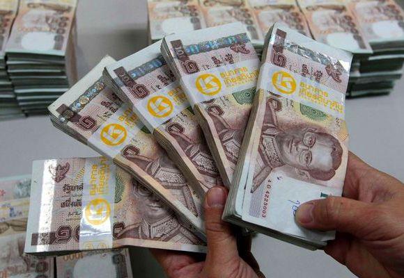 A bank employee counts Thai baht notes in Bangkok.