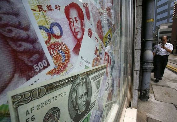 Photos of yuan (top) and US dollar banknotes are displayed at a money exchange in Hong Kong.