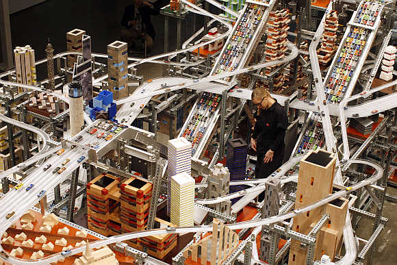 Alison Walker watches miniature cars move along the elevated freeway at Chris Burden's large-scale kinetic sculpture, Metropolis II, at the Los Angeles County Museum of Art, California.