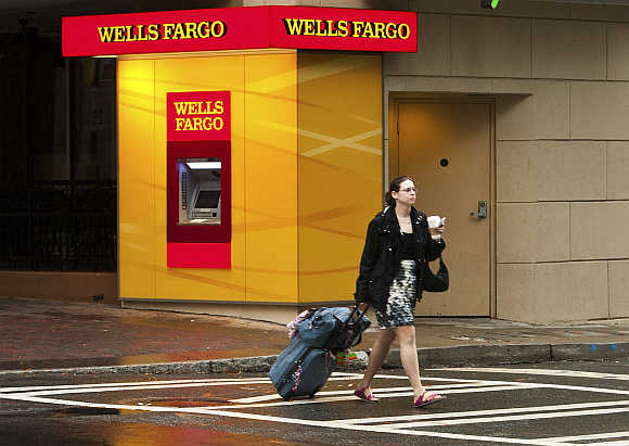 A woman crosses the street near a Wells Fargo automated teller machine in Charlotte, North Carolina, United States.