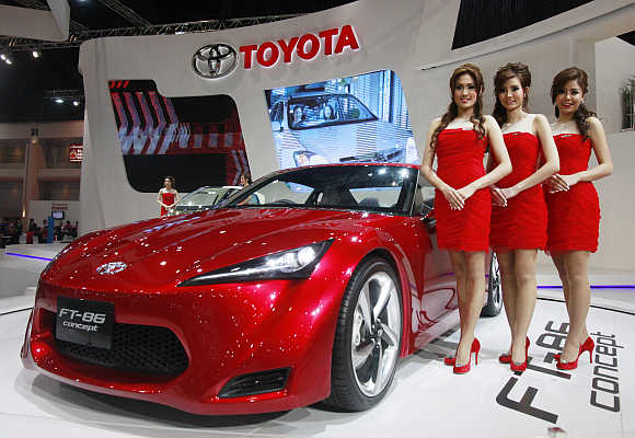 Models stand beside a Toyota FT-86 in Bangkok, Thailand.