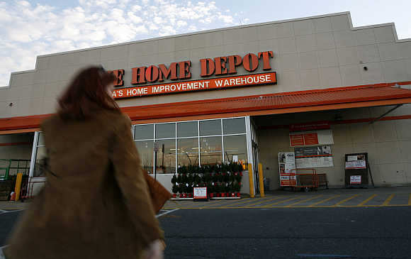 A woman walks towards a Home Depot store in Alexandria, Virginia, United States.