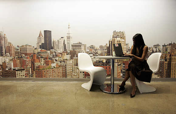 A Google employee works on a laptop in front of a mural of the New York City skyline.