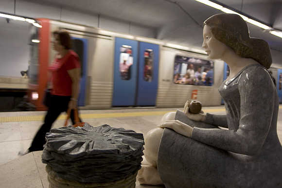 A passanger walks out of a Lisbon subway station decorated with sculptures.