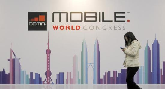 A visitor walks past a Mobile World Congress banner in Barcelona.
