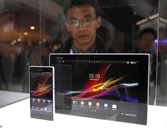 A visitor looks at the new Sony Xperia Z phone and tablet through a glass window during the Mobile World Congress in Barcelona.
