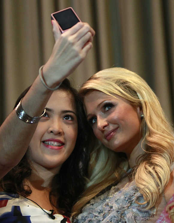 A fan uses her mobile phone to take a picture with Paris Hilton in Manila's Makati financial district.