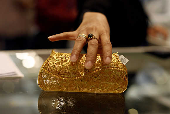 A visitor touches a mobile phone purse made of gold at the Jakarta International Jewellery Fair.