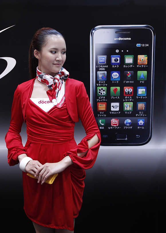 A campaign girl stands next to a billboard of Samsung Electronics' Galaxy S smartphone in Chiba, east of Tokyo.