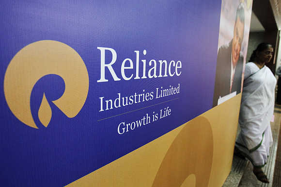 A woman walks past a poster of Reliance Industries in Mumbai.