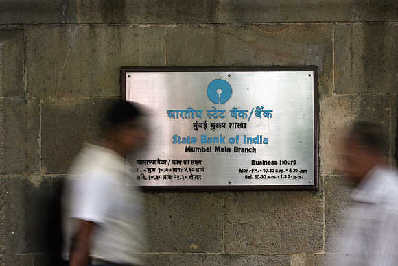 People walk in front of a signboard displayed at the head office of State Bank of India in Mumbai.