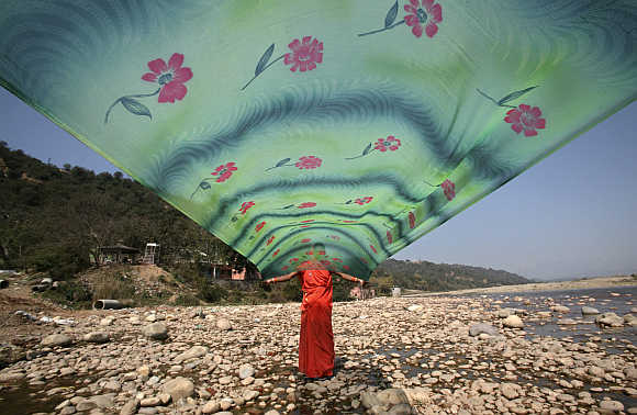 A woman dries her saree after washing it on the banks of river Tawi in Jammu.