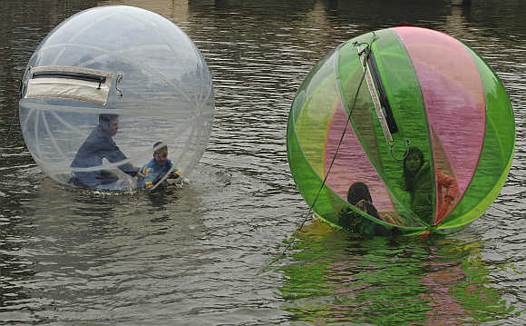 People float in balloons on a lake in Hanoi, Vietnam.