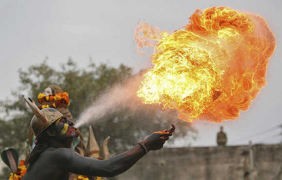 A man dressed as a demon performs with fire during a procession ahead of the Mahashivratri festival in Jammu.