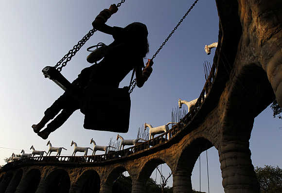 A women swings on rock arches at Nek Chand's Rock Garden in Chandigarh.