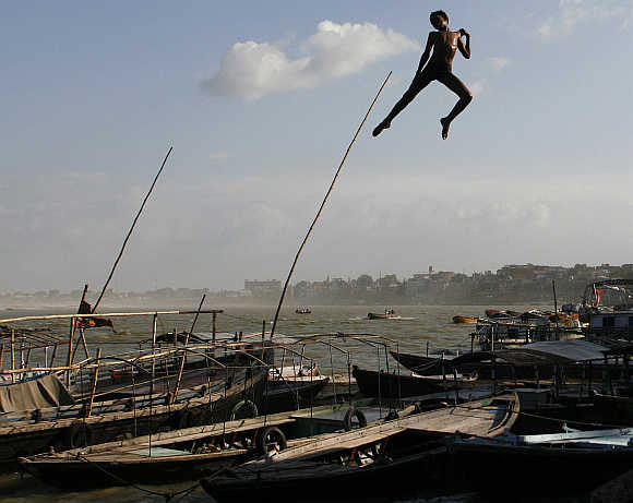 A boy jumps off a promenade into the river Ganges in Varanasi.
