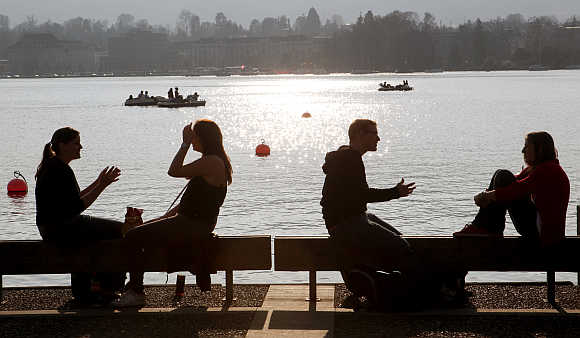 People enjoy the sunny spring weather as they sit on the banks of Lake Zurich in Zurich.