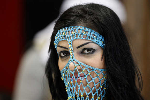 A girl in a transparent face veil attends the international tourism industry fair in Berlin.