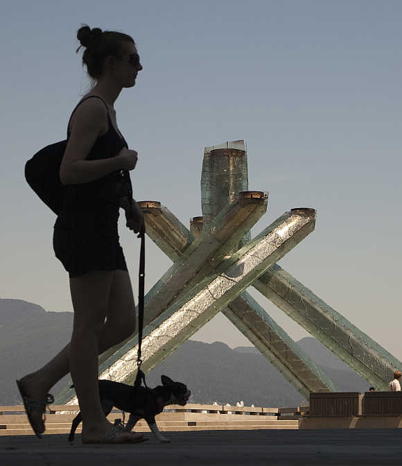 A woman walks past the Olympic Cauldron, one of the few signs left of the 2010 Olympic Winter Games held in Vancouver, British Columbia.