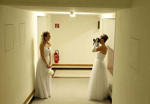 Dancers from the Young Ladies' Committee take photographs as they get ready prior to the opening ceremony at the traditional Opera Ball in Vienna.