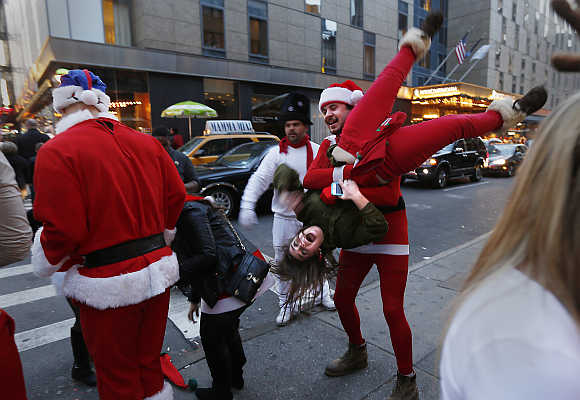 A man carries a woman upside down as other revelers walk down 8th Avenue during SantaCon in New York City.