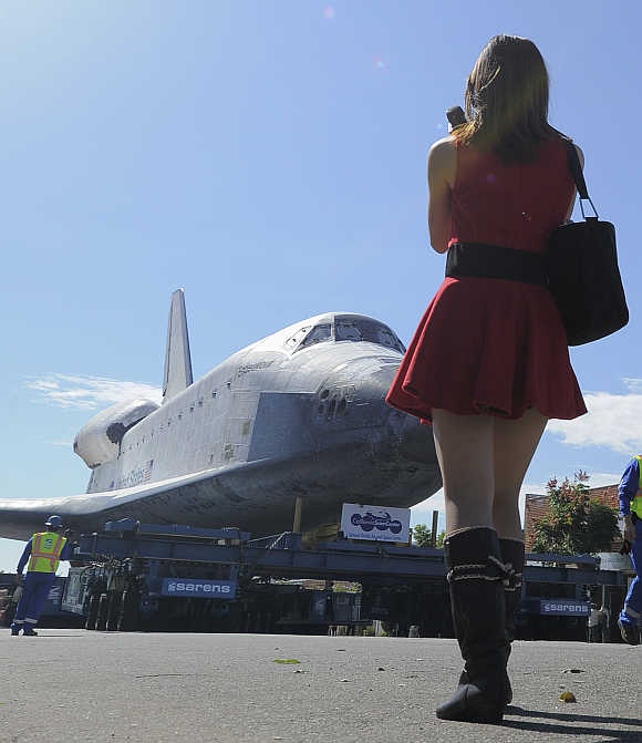 A woman watches as Space Shuttle Endeavour makes it way during its final ground journey in Los Angeles, California.