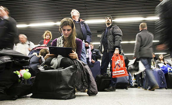 A woman watches a film as she waits at Frankfurt's airport.