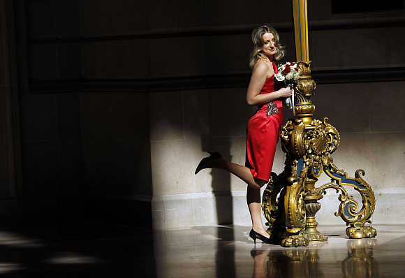 A woman wearing a red dress poses for a picture on Valentine's Day at City Hall in San Francisco.