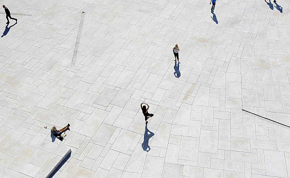 A woman poses for a picture in front of the Oslo Opera House.