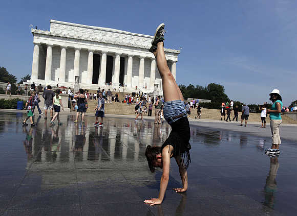 Sabrina Hatch of Idaho practices her handstand underneath sprinklers at the Lincoln Memorial in Washington, DC.