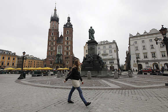 A woman walks in front of St Mary's Basilica in Krakow, Poland.